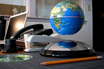 imag of work desk with globe, phone, stapler and computer
